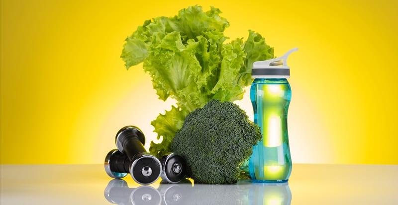 ירקות ירוקים, בקבוק מים ומשקוליות כושר